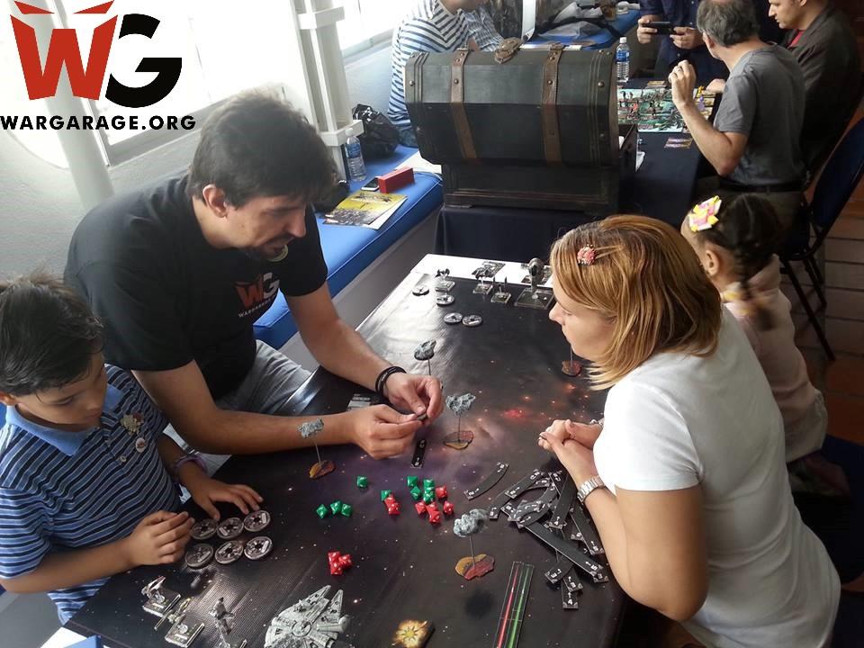 Familia aprendiendo a jugar Star Wars X-Wing Miniatures Game con uno de nuestros compañeros