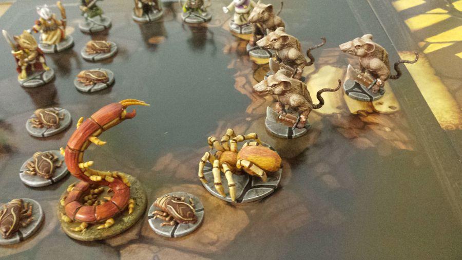 Otra foto de algunos enemigos y héroes de la caja básica encima de otra de las losetas del juego de mesa Mice and Mystics